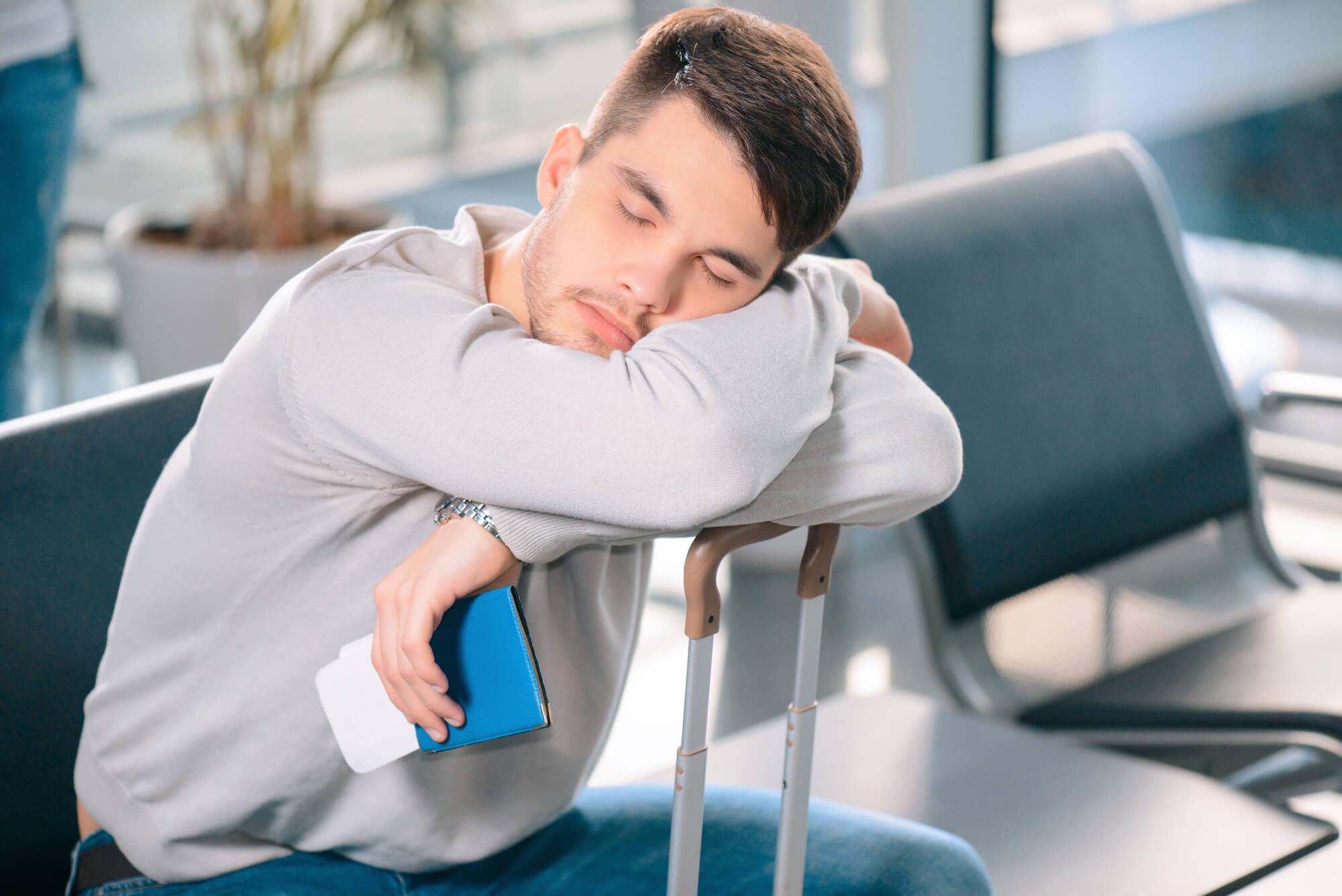 Homem dormindo em viagem no aeroporto